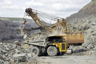 Mine worker with huge truck on the background